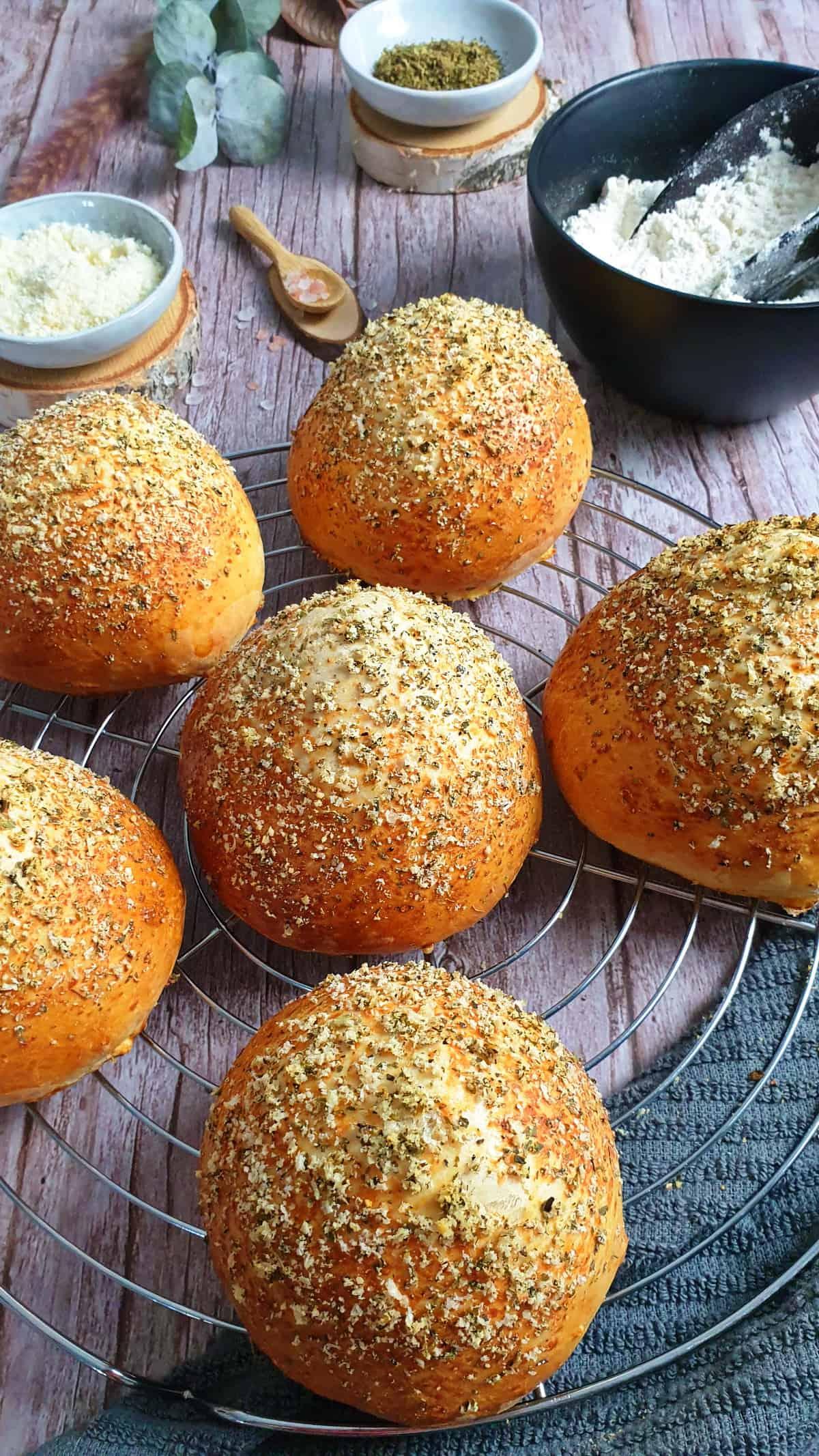 Auf einem Kuchengitter selbstgebackene Burger Brötchen mit Parmesan und Oregano Kruste. Im Hintergrund Deko.