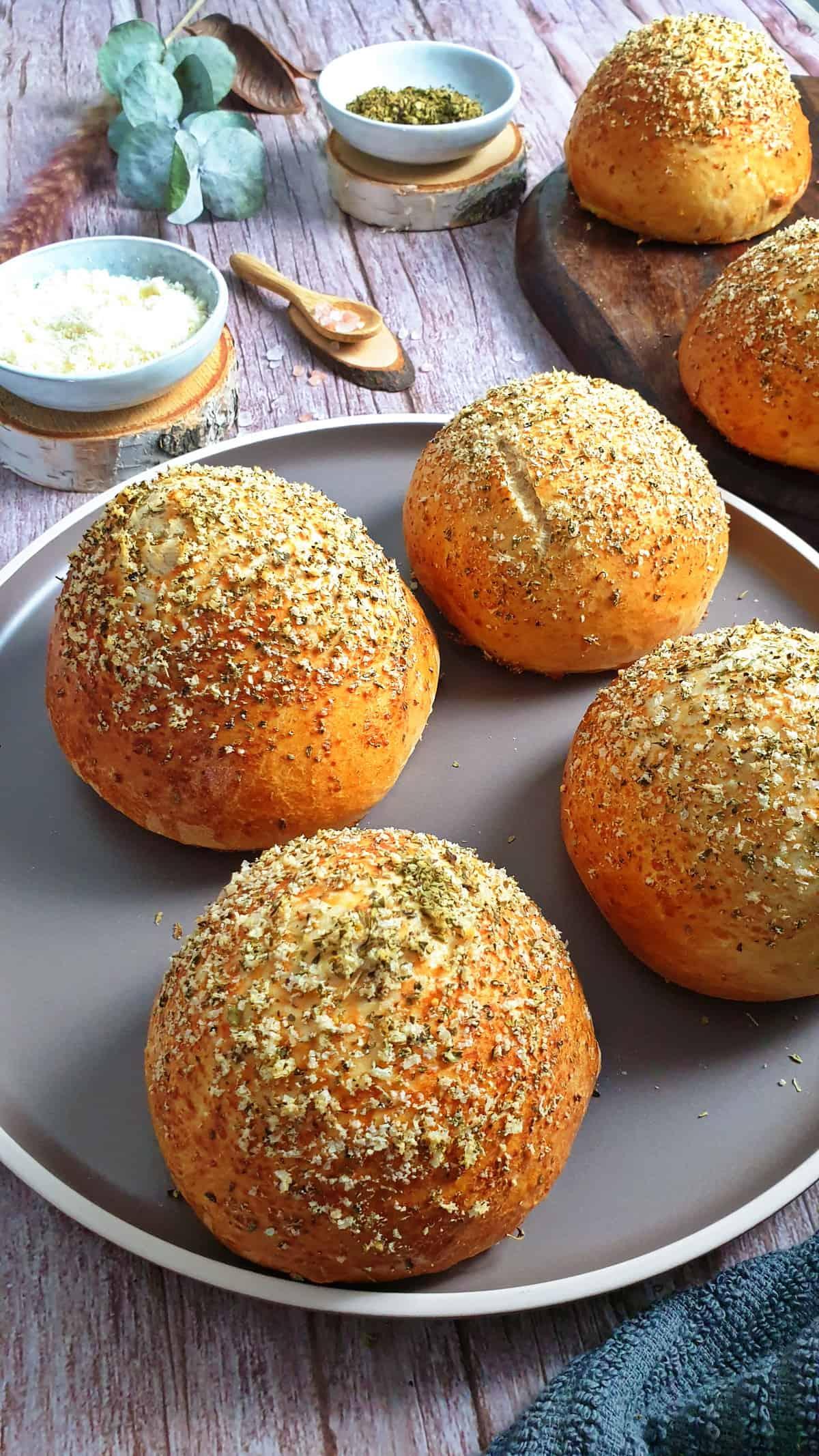 Auf einem braunen Teller vier Burger Brötchen mit Parmesan Oregano Kruste. Im Hintergrund Deko.