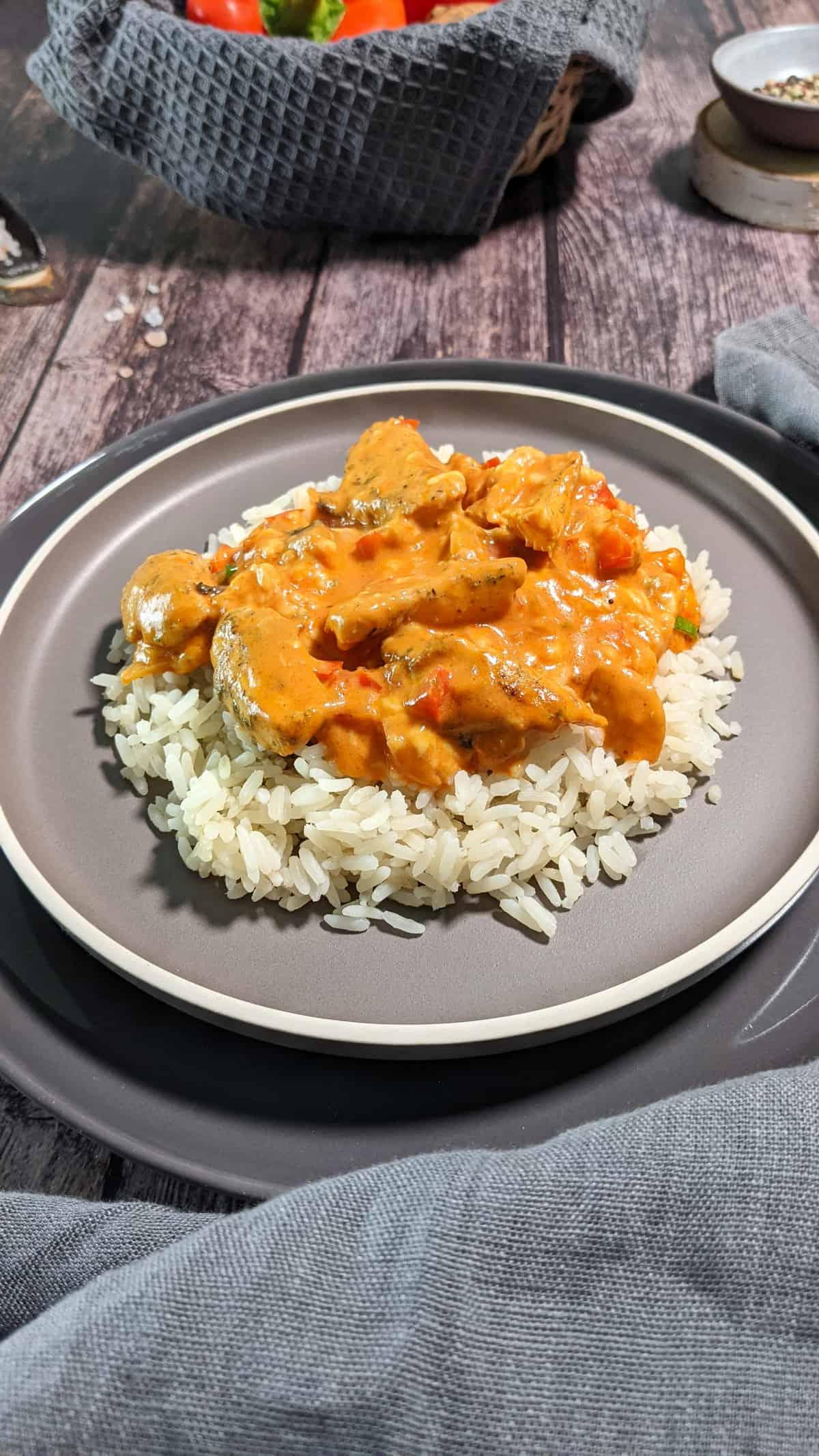 Auf einem grauen Teller Reis mit Gyros aus dem Ofen. Im Hintergrund Deko.