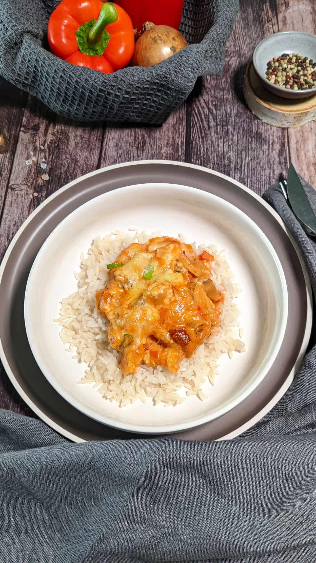Auf einem weißen Teller Reis mit Gyros aus dem Ofen. Im Hintergrund Deko.