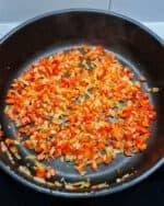 In einer Pfanne angedünstete Zwiebeln und Paprika-Würfel in Olivenöl.