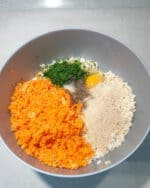 In einer grauen Schale Reis, Eier, Möhren und frische Kräuter.