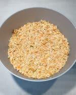 In einer grauen Schale eine vegetarische Masse aus Reis und Möhren für Frikadellen.