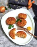 Auf einer weißen Servierplatte vegetarische Gemüse-Frikadellen aus Reis. Im Hintergrund Deko.