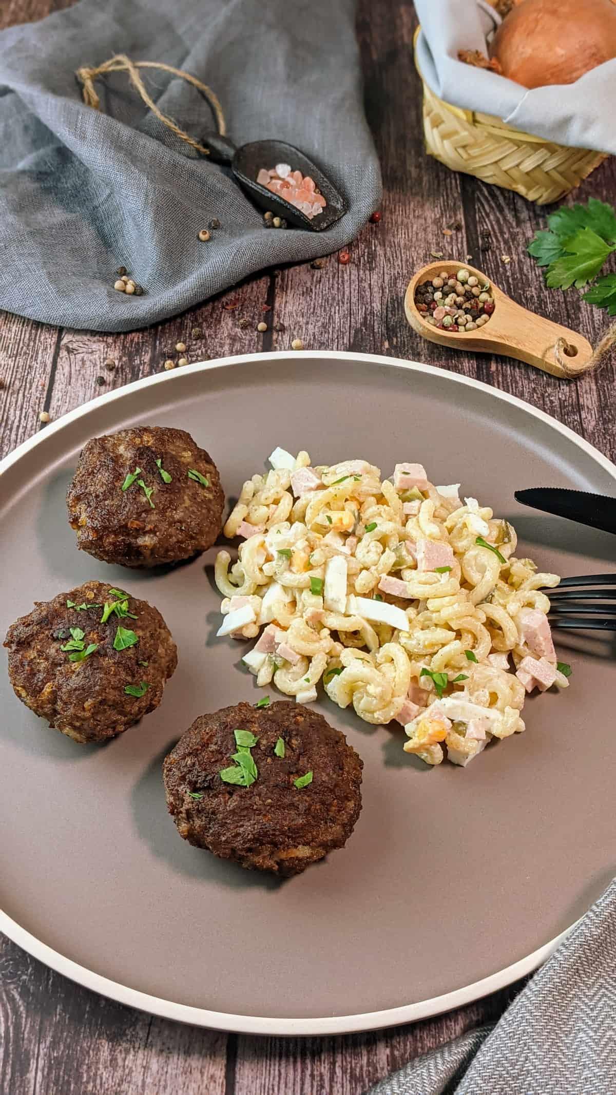 Auf einem braunen Teller ein selbstgemachter Nudelsalat mit Mayonnaise und drei Frikadellen. Im Hintergrund Deko.